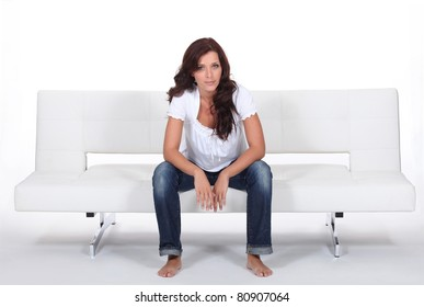 Casually dressed woman sitting on a white modern bed settee