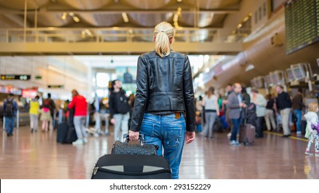 Casually dressed young stylish female traveller walking the airport terminal hall   draging suitcase and a handbag behind her. Blured background. Can also be used as railway, metro, bus station.