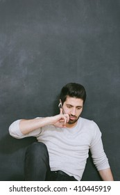 Casually handsome. Portrait of joyful young Arabic man standing against grey background.