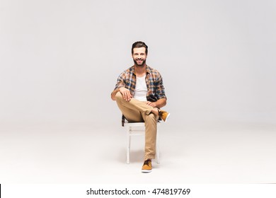 Casually handsome. Studio shot of handsome young man sitting on the chair and looking at camera with smile