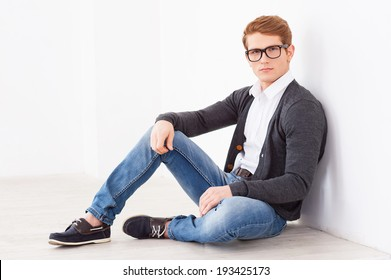 Casually handsome. Handsome young man in glasses looking at camera while sitting on the floor