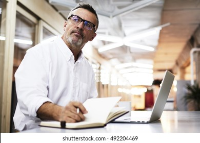 Casually-dressed mature businessman thinking about write news article while working late in an office. Creative editor is working on a new project. Skilled businessman in eye glasses making report