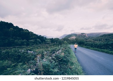 Casualy dressed hipster looking tourist walking down the countryside road and enjoing beautiful view on scenic mountain valley in rural uk.Human and nature.Tranquility and solitude concept.
