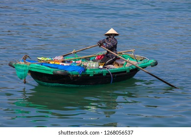 Cat Ba, Hai Phong, Vietnam - 11/23/2018:  Vendor from a floating village with her boat, trying to sell her products to the  tourists.