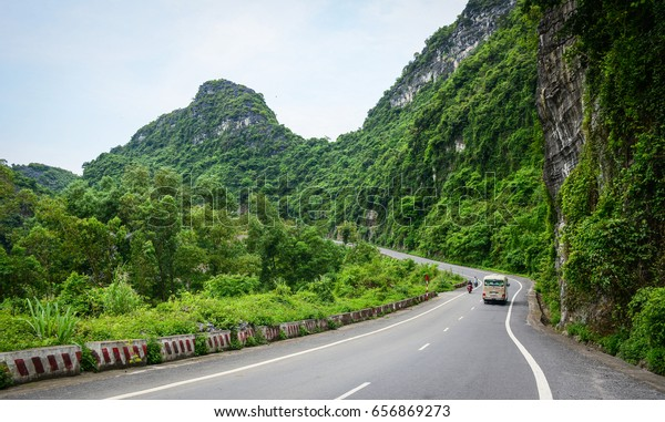 Cat Ba, Vietnam - May 22, 2016. Vehicles on rural road at Cat Ba Island in North of Vietnam. Cat Ba is an well-known archipelago with a spectacular array of sea and island scenery.