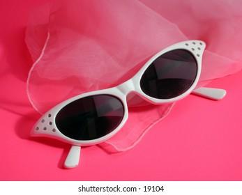 Cat eye sunglasses with pink chiffon scarf.