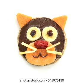 Cat face made out of pancake, melon, banana, strawberry and chocolate spread