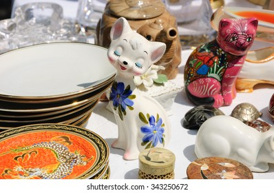 Cat figurines at flea market in Paris (France). Selective focus on the kitten with flowers.