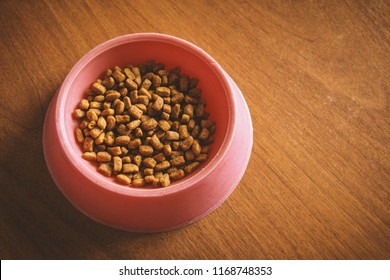 Cat food in a red plastic bowl on wooden background.
