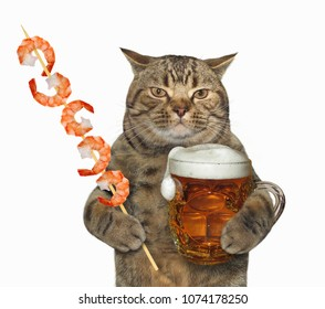 The cat in hat holds a glass mug of beer and a wooden skewer with shrimps. White background.