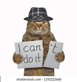 """The cat in a hat is tearing a piece of paper where writing the phrase """" I can't do it """". White background."""