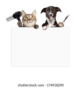 A cat holding a hair dryer and a dog holding cutting shears while hanging over a blank sign that is ready for you to enter your grooming service message on