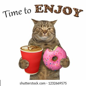 The cat holds a pink bitten doughnut and a cup of coffee. Time to enjoy. White background.