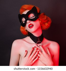 Cat mask. Redhead girl with bondage on black background. Sexual bdsm toy. Dominatrix model with red lips. Outfit for playing bdsm games. Lady with leather mask and dominatrix bondage on neck.