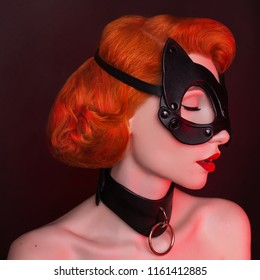 Cat mask. Redhead girl with bondage on black background. Sexual bdsm toy. Model with red lips. Outfit for playing bdsm games. Lady with leather mask and bondage on neck. Photo in low key lighting.