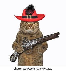 The cat musketeer in a red hat with a feather holds a flintlock pistol. White background. Isolated.