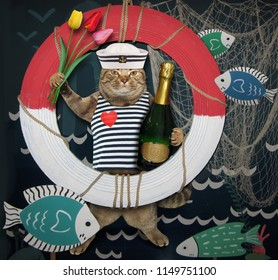 The cat sailor with a bottle of wine and tulips is standing next to a lifebuoy and a fishing net.