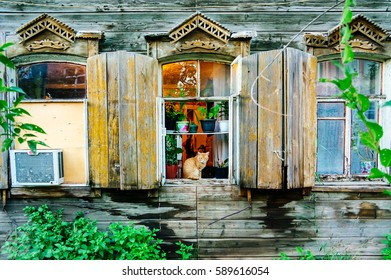 A cat sitting on a window of old traditional wooden building in Astrakhan, Russia.
