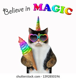 The cat unicorn is eating a big bitten color ice cream. Believe in magic. White background. Isolated.