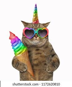 The cat unicorn in glasses is holding rainbow ice cream. White background.