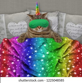 The cat unicorn with a green funny sleep mask is in the bed.
