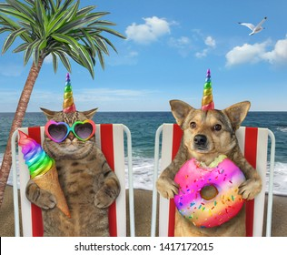 The cat unicorn in sunglasses is eating ice cream cone and dog unicorn is eating a colored donut. They sit under the palm tree on a beach chairs by the sea together.