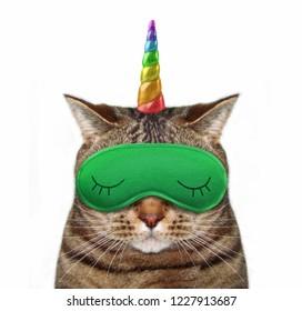 The cat unicorn wears a green sleep mask. White background.