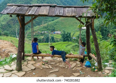 Cat Cat, Vietnam - August 20, 2017: Vietnamese children playing on bamboo swing with mountain rice terraces on the background