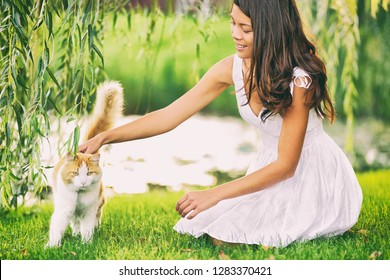 Cat woman cute spring portrait petting her animal outsisde in garden grass green park. Asian girl pet owner caressing kitten. Summer lifestyle outdoor.