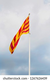 Catalan flag in Barcelona. Catalan flag waving in the wind on the background of the pre-storm sky.