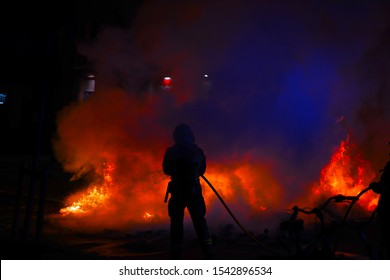 Catalan protest for independence, people breaking public facilites and fighting police. Burning  dustbin ! Firemen silhouettes fighting against the flames.