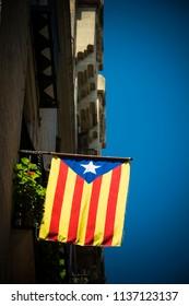 Catalonia flag against blue sky on streets of Barcelona