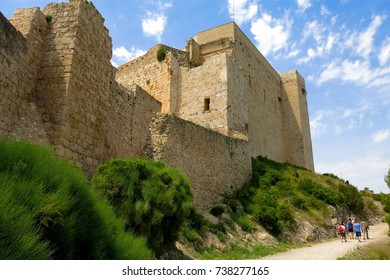 CATALONIA, SPAIN – JUNE 10, 2016: Hikers walk up a gravel path to medieval Miravet Castle, once occupied by the Knights Templar, in Miravet, Catalonia, Spain.
