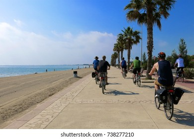 CATALONIA, SPAIN – JUNE 8, 2016: Cyclists bicycling beside beach beneath palm trees on coastal seaside bicycle path in L'Ampolla, Catalonia, Spain on a sunny day.