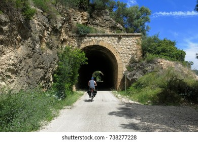 CATALONIA, SPAIN – JUNE 9, 2016: A cyclist prepares to enter a tunnel on the Via Verde trail in Catalonia, Spain.