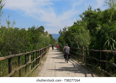 CATALONIA, SPAIN – JUNE 9, 2016: Cyclists and a lone hiker navigate the Via Verde trail in Catalonia, Spain.