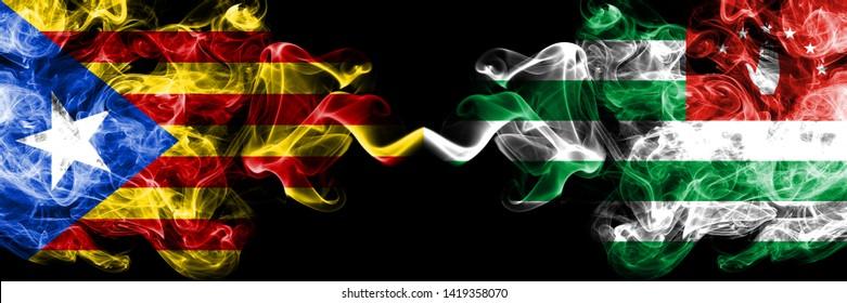 Catalonia vs Abkhazia, Abkhazian smoke flags placed side by side. Thick colored silky smoke flags of Catalonia and Abkhazia, Abkhazian
