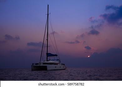 Catamaran anchoring on open ocean in dark sunset light, Maldives, Indian ocean
