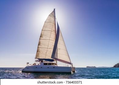 Catamaran backlit with sun behind the sail