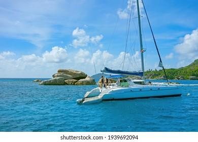 catamaran in a bay in the Seychelles, little Island with palm trees with granite rocks in the ocean