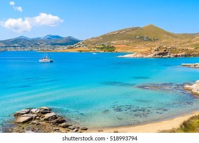 Catamaran boat saiing on azure sea in Monastiri bay on Paros island, Greece