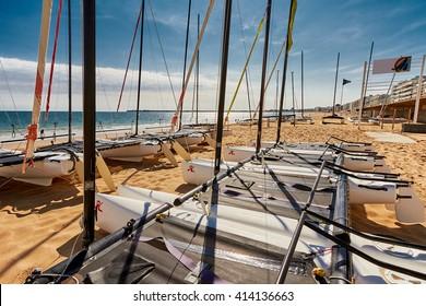 Catamaran empty. Catamaran stored on beach in La Baule France on blue sky.
