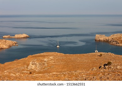 A catamaran enters in the quiet bay of Lindos, Greece
