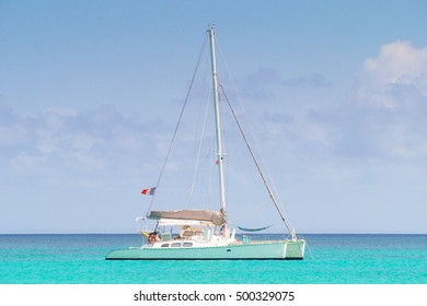 Catamaran with french flag anchored in a turquoise caribbean sea.