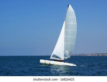 Catamaran in mediterranean sea on blue sky background