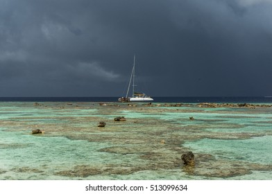 Catamaran on dark clouds, French Polynesia, Teriaroa