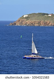 catamaran with passengers near Caribbean island surrounded by blue water