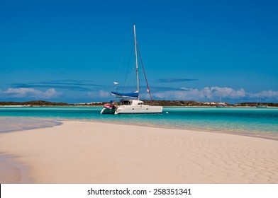 Catamaran sailboat anchored or moored in the turquoise tropical waters with white sand beach in the foreground