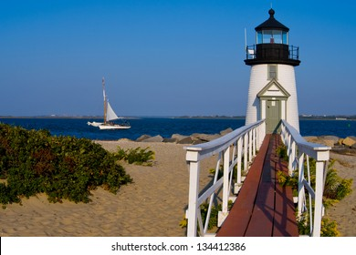 Catamaran sailboat near Brant Point Lighthouse. It is the most often rebuilt lighthouse at an astounding nine times. It is a favorite summer vacation on Nantucket Island in Massachusetts.