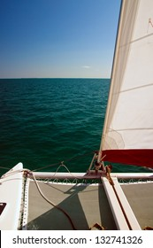 Catamaran sailboat with white and red set sail, sailing on a beautiful cloudless blue sky day and calm ocean waters